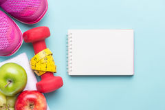 与哑铃的健身框架和果子复制空间-秀丽和体育在深蓝蓝色背景 图库摄影