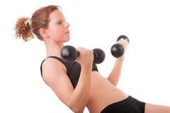与哑铃的少妇锻炼 免版税库存照片