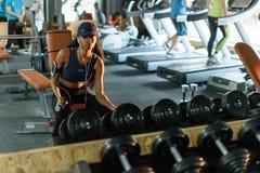 与哑铃的性感的黑非裔美国人的健身辅导员训练在健身房 免版税库存图片