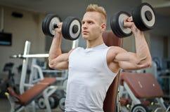 与哑铃的有吸引力的年轻人训练在健身房 库存图片