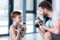 与哑铃的男孩训练与教练一起 免版税库存照片