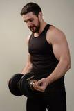 与哑铃的肌肉人锻炼 他执行供选择二头肌卷毛 库存图片