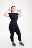 与哑铃的肥胖妇女锻炼 免版税图库摄影