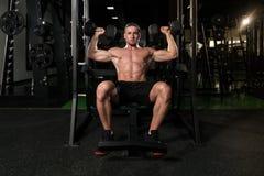 与哑铃的肩膀锻炼在健身房 库存照片