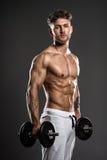 与哑铃的英俊的年轻爱好健美者训练,在灰色后面 图库摄影