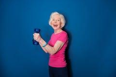 与哑铃的资深健身妇女训练在蓝色 免版税图库摄影