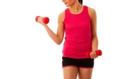 与哑铃的活跃少妇锻炼在健身健身房孤立 免版税库存图片
