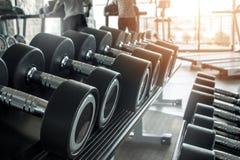 与哑铃行的健康生活方式健身概念和在健身房和一位个人教练员生活方式概念的肌肉Bu的 库存照片