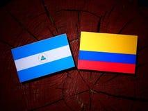 与哥伦比亚的旗子的尼加拉瓜的旗子在被隔绝的树桩 皇族释放例证