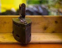 与哺养在一张木桌上的煤炭的古色古香的铁 库存图片