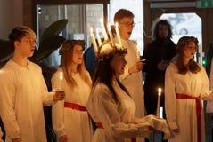 与唱歌的女孩和男孩的露西娅游行白色礼服holdin的 免版税库存照片