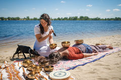 与唱歌的美好的女性接受能量合理的按摩在河岸滚保龄球 库存图片