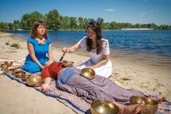 与唱歌碗和身体按摩的美好的女性接受能量合理的按摩在河岸 免版税库存图片