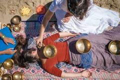 与唱歌碗和身体按摩的美好的女性接受能量合理的按摩在河岸 免版税图库摄影