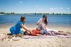 与唱歌碗和身体按摩的美好的女性接受能量合理的按摩在河岸 图库摄影