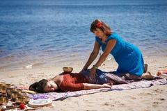 与唱歌碗和身体按摩的美好的女性接受能量合理的按摩在河岸 库存照片