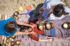 与唱歌碗和身体按摩的美好的女性接受能量合理的按摩在河岸 免版税库存照片