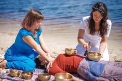 与唱歌碗和身体按摩的美好的女性接受能量合理的按摩在河岸 库存图片