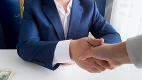 与商人握手在办公室和给贿款的人的特写镜头图象 库存图片