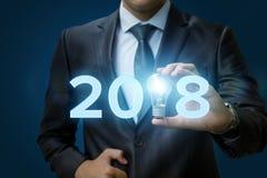 与商人的2018个想法概念递拿着电灯泡 库存图片