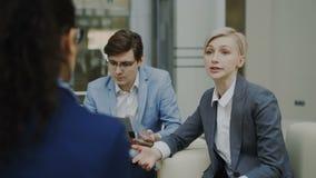 与商务伙伴的女实业家谈的和duscussing的未来成交坐长沙发在现代办公室中心 股票视频
