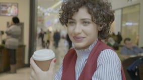 与啜饮从杯子的嫉妒的美好的女性模型微笑和看在购物中心咖啡店的照相机- 股票录像