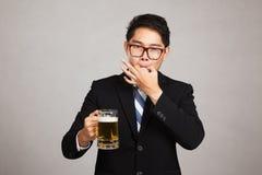 与啤酒口哨的亚洲商人与手指 免版税图库摄影