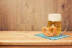 与啤酒杯和椒盐脆饼的慕尼黑啤酒节德国啤酒节日背景在木桌上 免版税库存照片