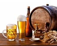 与啤酒杯的啤酒桶在一张木表。 图库摄影
