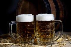 与啤酒杯的在黑背景的静物画和桶 库存照片