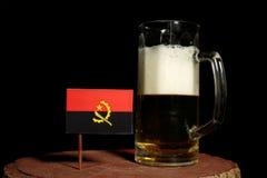 与啤酒杯的安哥拉旗子在黑色 免版税库存图片