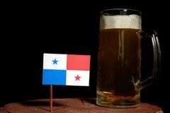 与啤酒杯的巴拿马旗子在黑色 库存照片