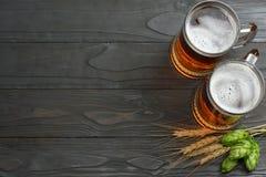 与啤酒花球果树和麦子耳朵的玻璃啤酒在与拷贝空间的黑暗的木背景 啤酒啤酒厂概念 背景啤酒包含梯度滤网 免版税库存照片