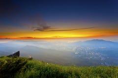 与喜怒无常的云彩的日落山 免版税库存图片