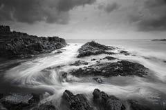 与喜怒无常的天气和打旋的海洋的海景流动 图库摄影