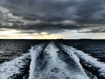 与喜怒无常的天空的小船苏醒 免版税库存照片