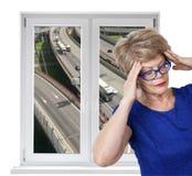 与喧闹的高速公路室外和资深妇女的被打开的双门pvc窗口有在屋子里面的头疼的 库存照片