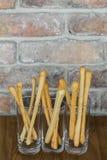 与喷口的传统意大利家庭做的grissini在与拷贝空间的土气砖墙背景 免版税库存图片