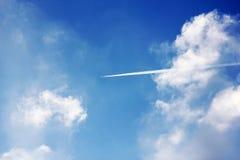 与喷气机足迹的多云蓝天 库存照片