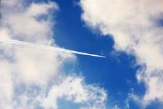 与喷气机足迹的多云蓝天 免版税库存照片