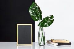 与嘲笑的时髦的内部海报框架,在玻璃瓶的叶子在与黑白墙壁的桌上在背景 库存图片