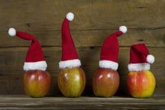 与四个红色圣诞老人帽子的滑稽的圣诞节贺卡在苹果 库存照片