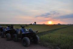与四个轮子摩托车的日落视图 免版税库存图片