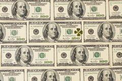 与四叶三叶草的背景由一百美元钞票做成 库存照片