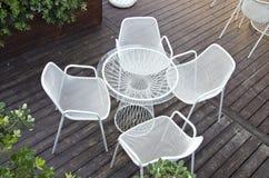 与四把椅子的玻璃桌在户外围场 免版税库存照片