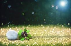 与四片叶子幸运的三叶草和石头的抽象背景 库存图片