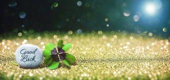 与四片叶子幸运的三叶草和石头的抽象背景 免版税库存照片