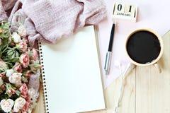 与围巾、笔记本纸、立方体日历和咖啡杯的书桌桌 免版税库存照片