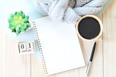 与围巾、笔记本纸、辅助部件、立方体日历和咖啡杯的书桌桌 库存图片