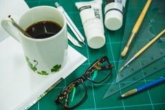 与固定式对象的笔记薄艺术品和热的咖啡的 图库摄影